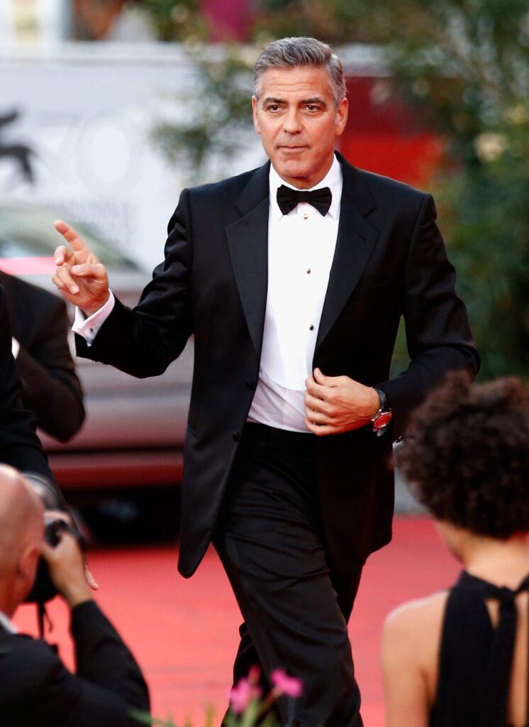 George Clooney com um terno caminhando em tapete vermelho